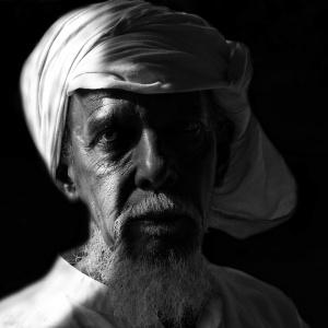 Portrait of an old man, wrinkled face under low light. Dark low light photography. Nikon D5600.